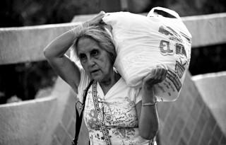 """Una persona anziana trasporta a spalla """"un ... sacco di viveri"""""""