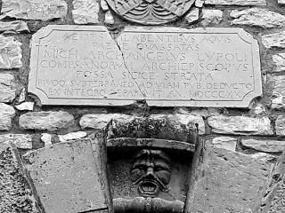Lapide e mascherone sul portale dell'Episcopio